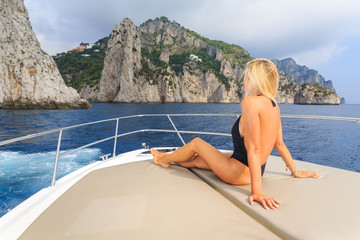 Young sexy woman enjoying on yacht at  island capri italy