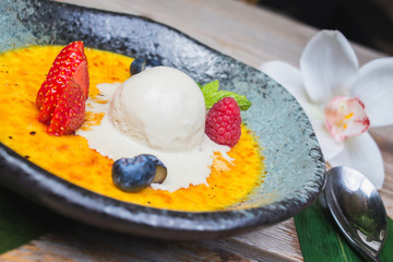 scoop of ice cream on a plate with fresh berries and creme