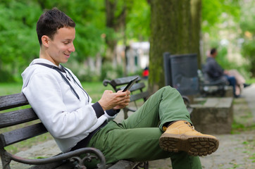 Young man sitting on the bench and using tablet device on beauti