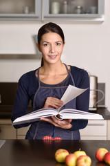 Frau mit Schürze blättert in einem Kochbuch