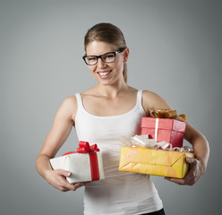 Pretty smiling female holding gift boxes. Christmas eve.