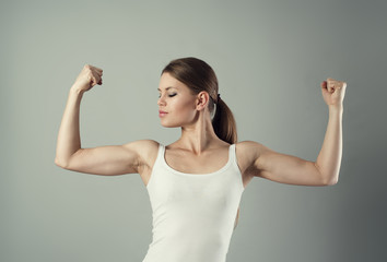 Young sporty female showing her biceps. Concept of strength.