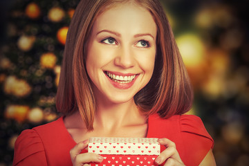 beauty girl in red dress with gift box to Christmas