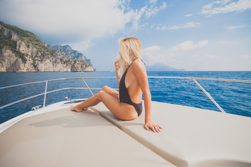 Young sexy woman enjoy on yacht at faraglioni island capri italy