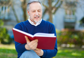 Man reading a book at the park