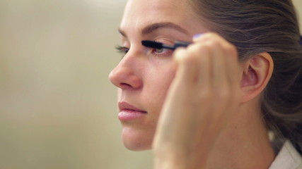 Young beautiful woman applying makeup on eyelid with brush