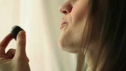 Close up of woman's lips biting a bar of chocolate