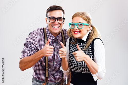 Happy nerdy couple showing thumbs up - 74731201