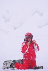 Bambino con lo snowboard sotto la neve