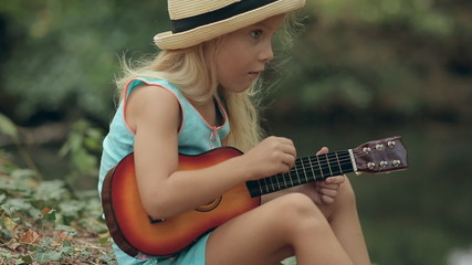 Little girl in a straw hat sitting in the forest near the river