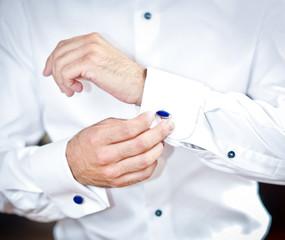 Man wears cuff-links on a shirt sleeve. Groom putting cuff-links