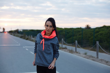 Fitness woman dressed standing on the road at sunset, attractive