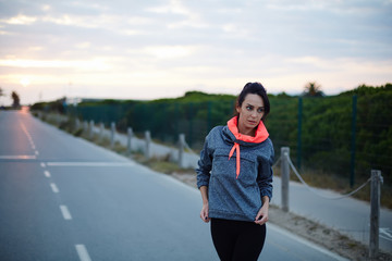 Fitness woman dressed in bi color hoodies standing at sunset