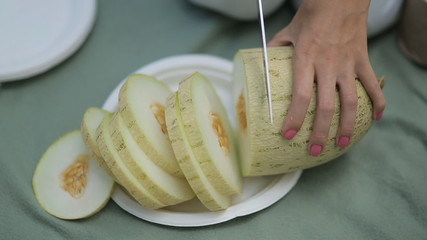 The girl with a knife cuts ripe juicy melon