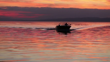 motorboat approaching the camera at sunset in silhouette
