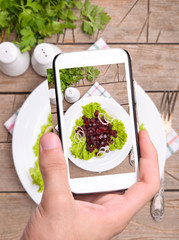 Hands taking photo beet salad with smartphone