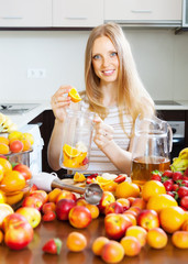 blonde housewife making beverage with fruits