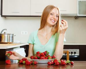 Positive blonde girl eating strawberry