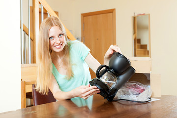 Smiling young blond unpacking new coffeemaker