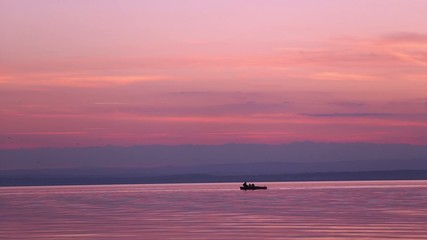 children on a boat on a lake sunset have fun in silhouette