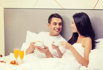 smiling couple having breakfast in bed in hotel
