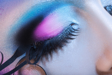 Macro photo of closed woman eye with multicolor make up