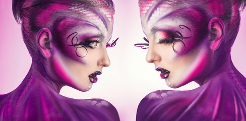 Horizontal photo of two women with creative magenta body art