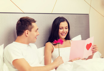 smiling couple in bed with postcard and flower
