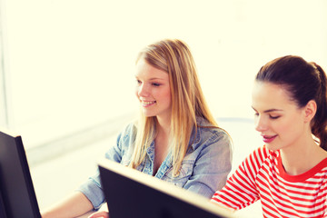 two smiling girls in computer class