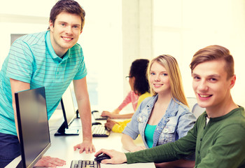 group of smiling students in computer class