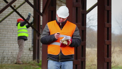 Worker with cell phone and with other worker in background