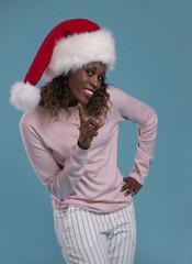 African woman wearing santa hat smiling