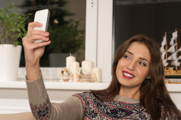 Young pretty woman taking selfie at home