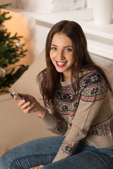 Happy woman at home reading a text message