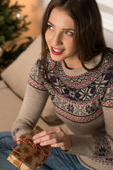 Winter woman sitting near Christmas tree at home and opening gif