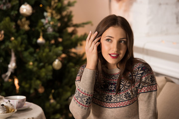 Woman wearing winter outfit sitting near Christmas tree