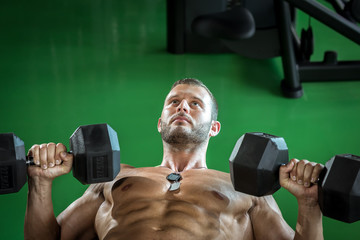 Man doing dumbbell press while lying down