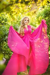 Woman dressed in pink gown walking in blooming garden