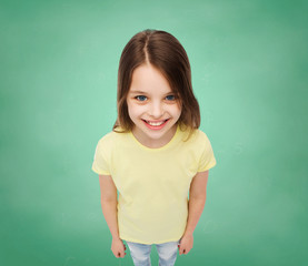 smiling little girl over green grass background