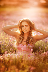 Sensual Woman Lying on a Meadow with Violet Flowers.