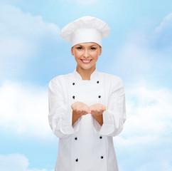 smiling female chef holding something on hands