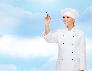 smiling female chef writing something on air