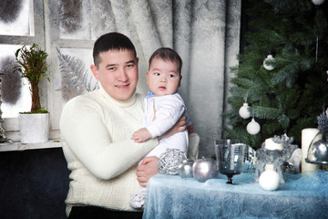 father with baby on a background of the Christmas tree for the h