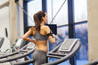 woman with earphones exercising on treadmill