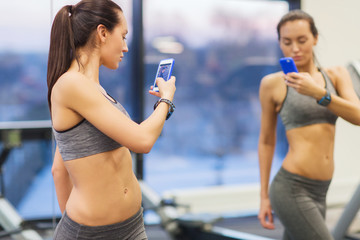 woman with smartphone taking mirror selfie in gym