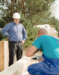 Architect or foreman watching a builder