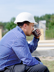 Young builder taking his coffee break