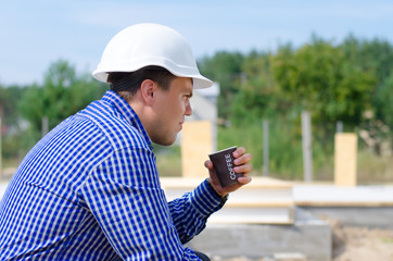 Young workman sipping coffee on a building site