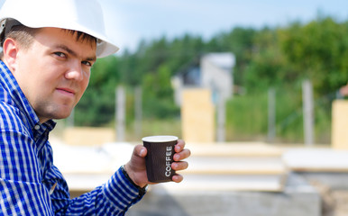 Workman drinking coffee in his hardhat