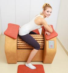 Girl in sportwear on relax massage equipment healthy spa salon